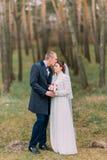 Het mooie enkel echtpaar stellen in groen naaldboomhout De bruidegom kust zacht zijn leuke bruid in voorhoofd volledig Stock Foto