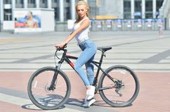Het mooie fitness meisje gekleed in uitrusting met sportfiets loopt stock afbeeldingen