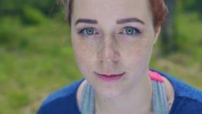 Het mooie freckled gezicht van jonge vrouwen groene ogen glimlacht in openlucht, sportuitrusting stock video