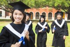Het mooie gegradueerde houdt een diploma met klasgenoten royalty-vrije stock foto