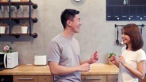 Het mooie gelukkige Aziatische paar danst thuis in de keuken Het jonge Aziatische paar heeft thuis romantische tijd het luisteren stock video