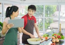 Het mooie gelukkige Aziatische paar kookt in de keuken bereid saladevoedsel voor diner voor Man en Vrouwen glimlachen die menu va stock foto