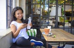 Het mooie gelukkige Aziatische vrouw ontspannen glimlachen genietend van ontbijt die mobiele telefoon met behulp van royalty-vrije stock fotografie