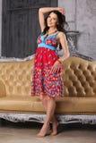 Het mooie gelukkige brunette in een heldere kleding bevindt zich dichtbij een leerbank Royalty-vrije Stock Afbeelding