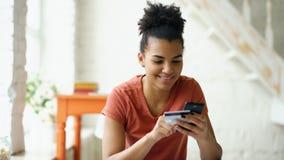 Het mooie gelukkige gemengde online bankwezen die van de rasvrouw smartphone gebruiken die online met creditcard thuis levensstij stock foto's
