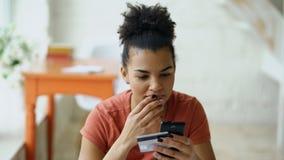 Het mooie gelukkige gemengde online bankwezen die van de rasvrouw smartphone gebruiken die online met creditcard thuis levensstij stock afbeelding