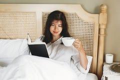 Het mooie gelukkige jonge boek van de vrouwenlezing en het drinken koffie in bed in hotelruimte of huisslaapkamer Modieus donkerb royalty-vrije stock foto