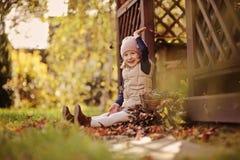 Het mooie gelukkige kindmeisje spelen met de herfstbladeren en het werpen van hen Royalty-vrije Stock Afbeelding