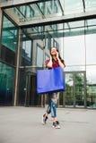 Het mooie gelukkige meisje gaat winkelend in de stad stock foto