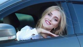 Het mooie gelukkige meisje kijkt uit het autoraam in de zomer stock videobeelden