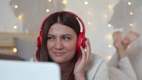 Het mooie gelukkige meisje ligt op het bed gebruikend een mobiele computer in wit en luistert aan muziek op hoofdtelefoons HD Clo stock videobeelden