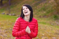 Het mooie, gelukkige meisje met verwaande glimlach in rood jasje is in het bos Royalty-vrije Stock Afbeeldingen