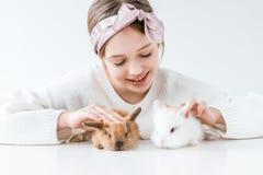 Het mooie gelukkige meisje spelen met aanbiddelijke bontkonijnen stock foto