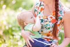 Het mooie gelukkige moeder openlucht de borst geven Stock Afbeeldingen