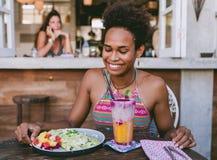 Het mooie gemengde meisje van de ras vreedzame eilandbewoner in vegetarische koffie voor ontbijt met omslag en salade en verse me royalty-vrije stock fotografie