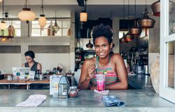 Het mooie gemengde meisje van de ras vreedzame eilandbewoner in vegetarische koffie voor ontbijt met verse mengeling smoothie in  royalty-vrije stock foto's