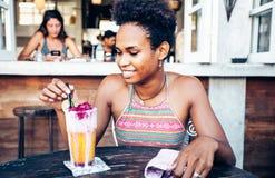 Het mooie gemengde meisje van de ras vreedzame eilandbewoner in vegetarische koffie voor ontbijt met verse mengeling smoothie in  royalty-vrije stock afbeelding