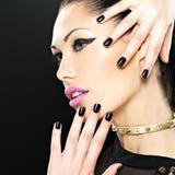 Het mooie gezicht van maniervrouw met zwarte spijkers en helder maakt Stock Foto's