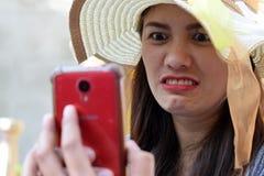 Het mooie Gezicht van middenleeftijdsvrouw die zondaghoed dragen ergerde boos gezicht doorbladerend Internet in smartphone stock afbeeldingen