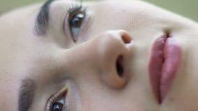 Het mooie gezicht van ogen van de vrouwen de pan, zachte huid en de lippen die van jong wijfje, vertragen liggen stock videobeelden