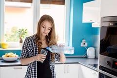 Het mooie gietende water van de blondevrouw van een fles in een glas Royalty-vrije Stock Foto