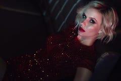 Het mooie glam blonde model met provocatief maakt omhoog het dragen van het rode lovertjekleding ontspannen op de bank in nachtcl stock foto's