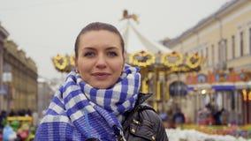 Het mooie het glimlachen brunette in warme sjaal bekijkt camera bij carrouselachtergrond stock videobeelden