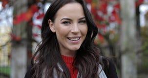 Het mooie het glimlachen vrouw stellen in park stock footage