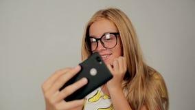 Het mooie glimlachende blondemeisje draagt glazen makend selfie door smartphone stock footage