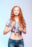 Het mooie glimlachende roodharigemeisje blaast bellen. Studioportret Royalty-vrije Stock Foto