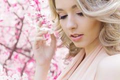 Het mooie heldere jonge gelukkige leuke meisje loopt in het park dichtbij de roze bloeiende boom in een zonnige dag Stock Foto