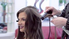 Het mooie het glimlachen brunette in schoonheidssalon, kapper doet stijl haar haar stock footage