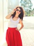Het mooie het glimlachen donkerbruine vrouw dragen rode zonnebril en rok Stock Foto