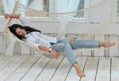 Het mooie het glimlachen jonge vrouw ontspannen in hangmat thuis royalty-vrije stock fotografie