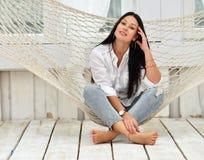 Het mooie het glimlachen jonge vrouw ontspannen in hangmat thuis stock afbeeldingen
