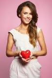 Het mooie het hart van de vrouwenholding glimlachen aanbiddelijk in roze Royalty-vrije Stock Foto
