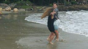 Het mooie het houden van paar kussen op het strand die dan holdingshanden wervelen stock footage