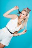 Het mooie het meisjes retro stijl van de blondevrouw pinup stellen op blauw stock afbeeldingen