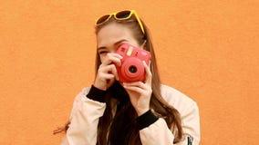 Het mooie hipstermeisje maakt foto door onmiddellijke camera Oranje Achtergrond openlucht stock videobeelden