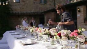 Het mooie huwelijkslijst plaatsen Dient het kelners gediende huwelijk in Feestelijke lijst in het restaurant stock video