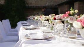 Het mooie huwelijkslijst plaatsen Kelners gediende die huwelijkslijst met bloemen wordt verfraaid Feestelijke lijst in het restau stock footage