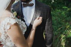 Het mooie huwelijkspaar in het bos de bruid raakt de bruidegom teder in vlinderdas Huwelijksknoopsgat en geruit kostuum binnen stock foto