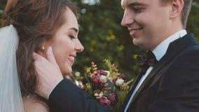 Het mooie huwelijkspaar in greep, kijkt en streelt elkaar stock videobeelden