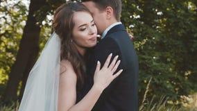 Het mooie huwelijkspaar in greep, kijkt en streelt elkaar stock video