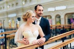 Het mooie huwelijkspaar in Moskou, de bruid en de bruidegom in een wit kleden zich in de binnenlandse, gelukkige nieuwe familie Stock Fotografie