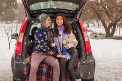 Het mooie internationale paar ontspannen in aard in de winter Romantische vergadering van een paar in liefde in de sneeuw Het jon stock afbeeldingen
