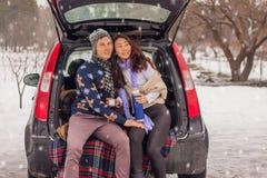 Het mooie internationale paar ontspannen in aard in de winter Romantische vergadering van een paar in liefde in de sneeuw Het jon royalty-vrije stock afbeelding