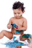 Het mooie jong geitje spelen met zijn schilderijen Stock Afbeelding