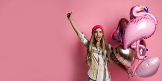 Het mooie jonge blije meisje houdt een bos van roze ballons op een roze pastelkleurachtergrond royalty-vrije stock afbeelding