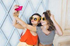 Het mooie jonge blonde en het brunette van paar modieuze meisjes in een heldere gele kleding en zonnebril die en voor ca stellen  Stock Foto